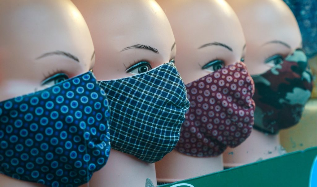 A closeup of a line of mannequin heads wearing patterned fabric masks.