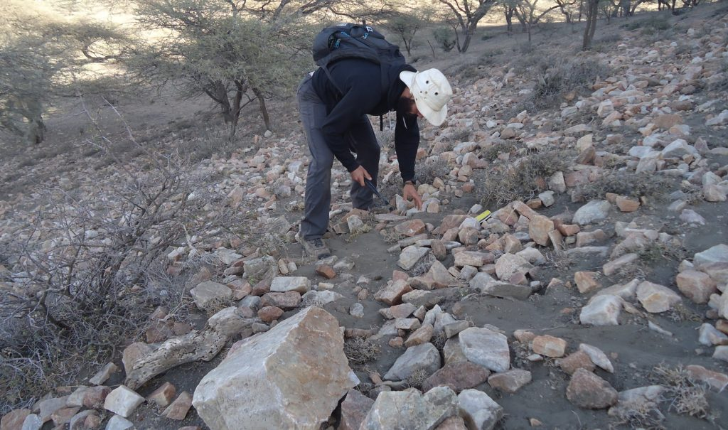 Julien Favreau is bending over to touch a rock. He's standing on a slope covered in rocks.
