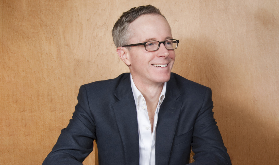 The photo is of a smiling man wearing glasses, a white shirt and a suit jacket