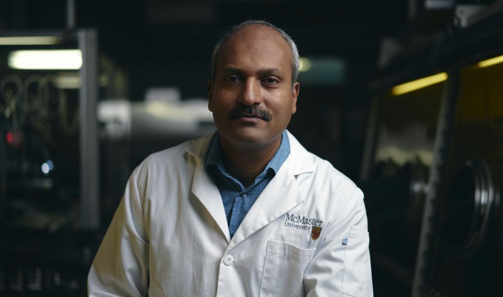 A man sitting on a stool in a dark lab, slightly smiling
