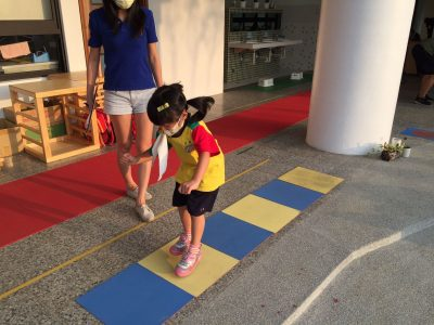 A child jumps on flat blue and yellow foam squares on the ground. She is getting her coordination assessed by a researcher who stands beside her