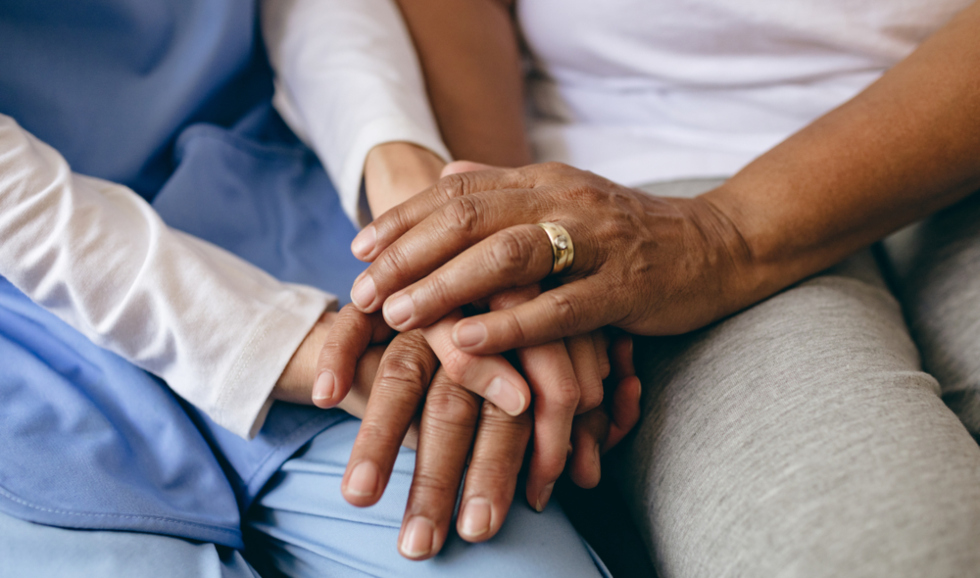 lose up of an older person's hands holding a younger person's hands
