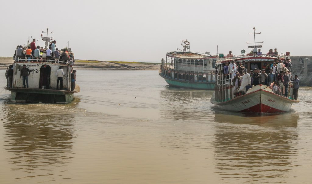 Ferries full of people on a muddy river.