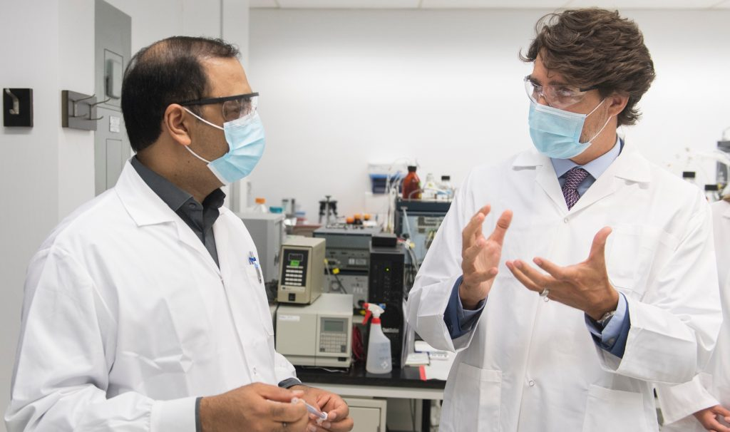 Scientist and Trudeau, both wearing lab coats and covid masks, talking.