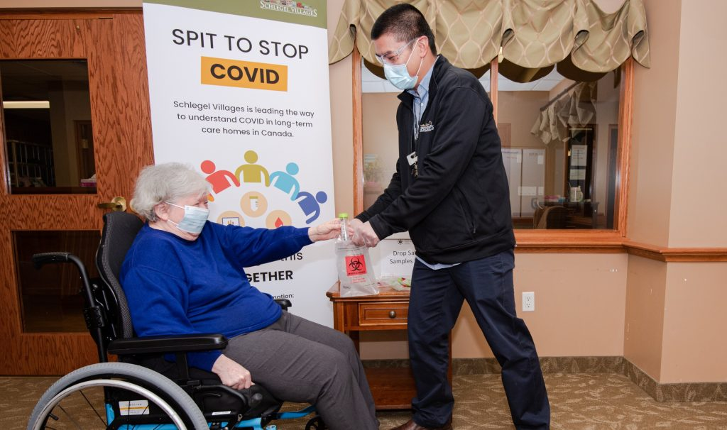 An older woman wearing a mask in a wheelchair hands a vial to a medical worker. They're in front of a sign about spit tests for COVID