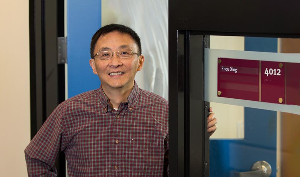 Zhou Xing standing in the doorway of his office.