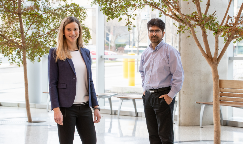 McMaster University researchers Ali Ashkar and Sophie Poznanski stand in an atrium.
