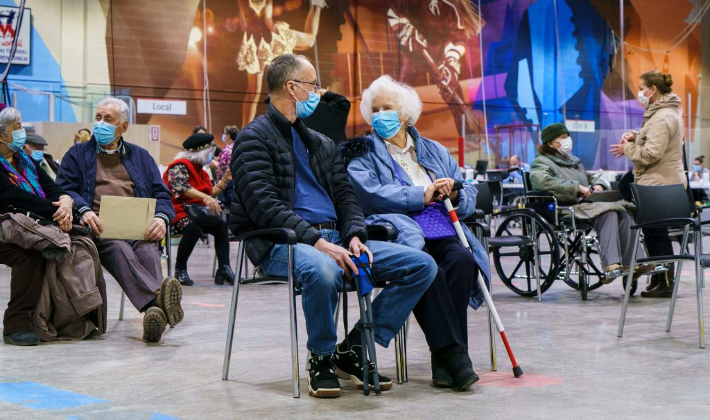 Masked older adults sitting waiting in chairs that are spaced out for distancing.