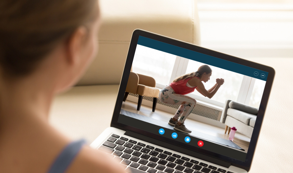 Over-the-shoulder image of a woman watching a fitness class on her laptop.