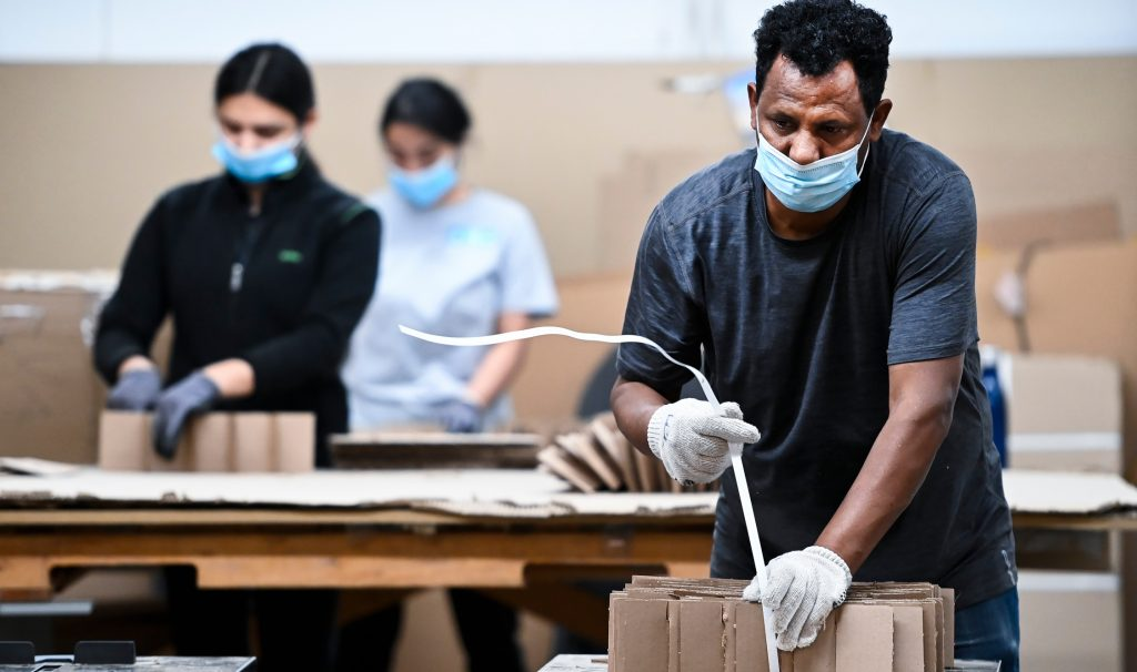Masked, gloved workers package cardboard objects.