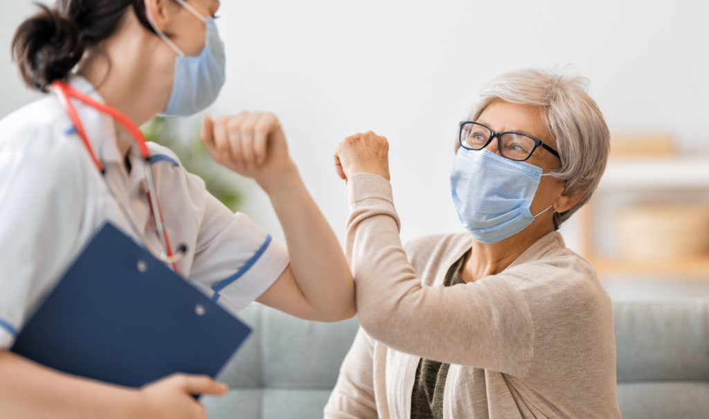 Masked health-care worker holding clipboard bumps elbows with masked older adult.