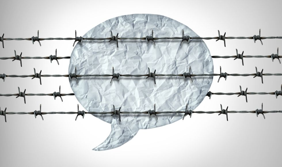 Illustration of a speech bubble behind rows of barbed wire.