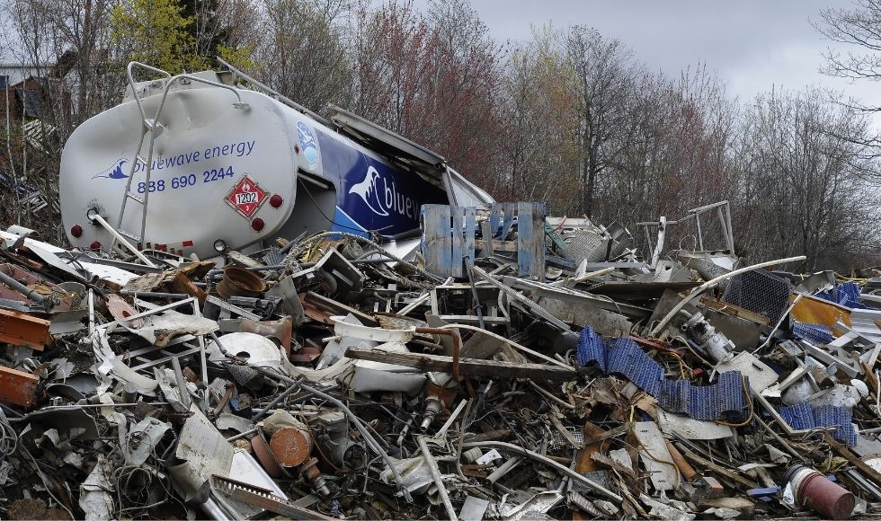 A tanker truck rest on a heap of other metal and wood waste in a dump.