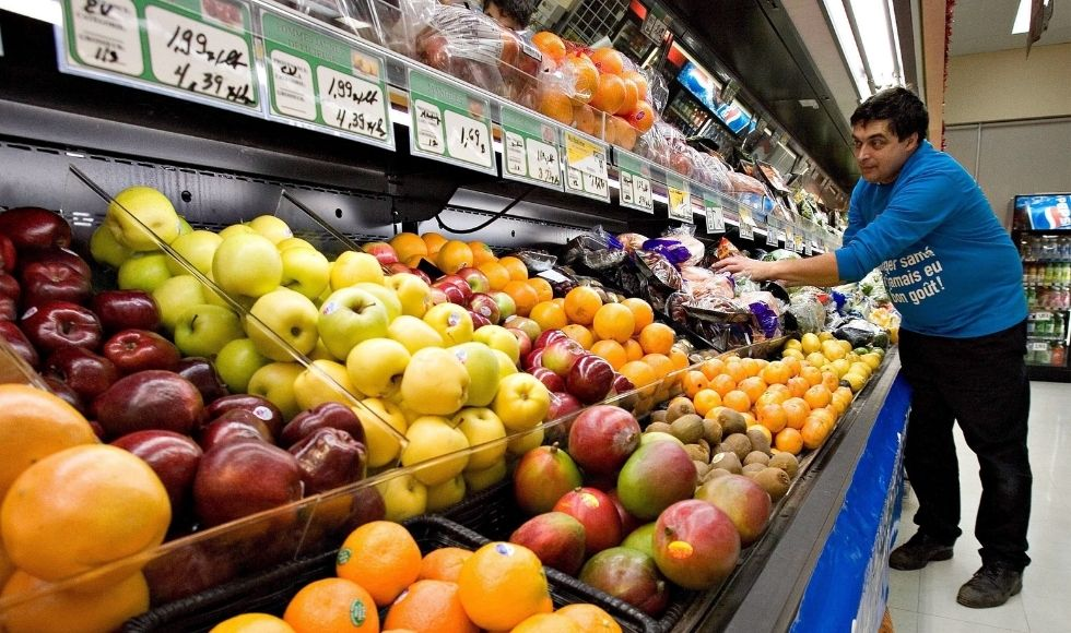 A grocery store worker stocks shelves of fruit