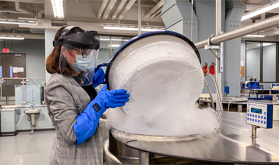 Woman in mask, face shield, protective gloves lifts up a lid to release a lot of dry-ice smoke in a lab setting.