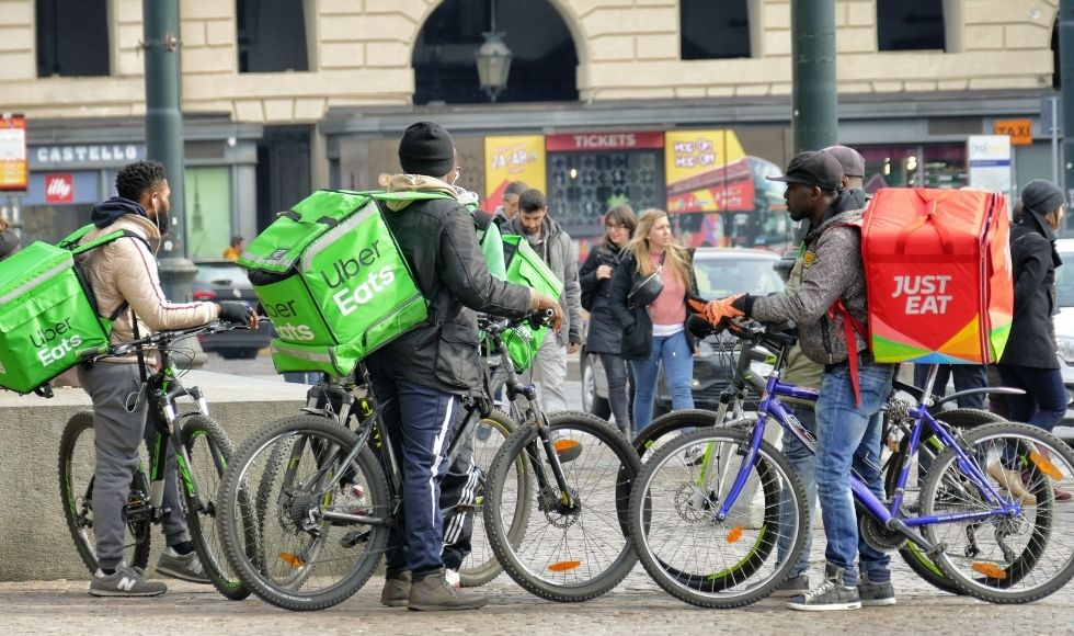 A group of food-delivery bicycles and riders.