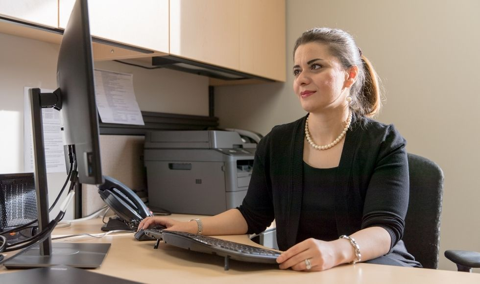 A woman sitting at a computer desk.
