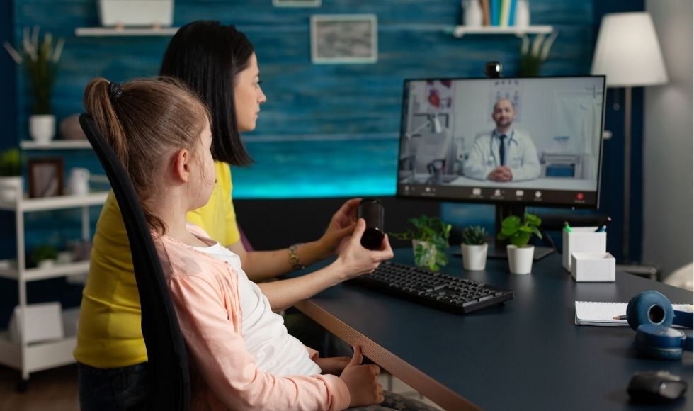An adult and a child sitting at a computer, talking to a man in a lab coat on the screen.